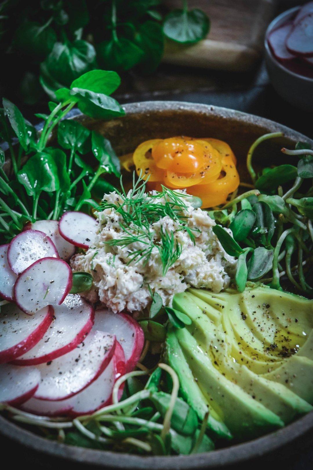 Tuna salad on plate with avocado, orange pepper, greens and sliced radishes